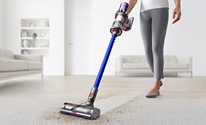 A woman cleaning hard floor and carpet with a Dyson V11™ vacuum